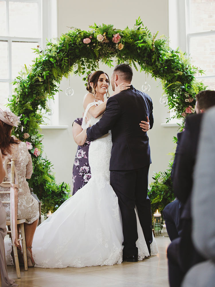couple-marriage-under-greenery-ceremony-arch