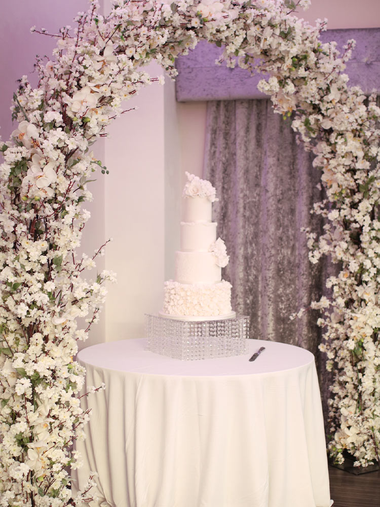 floral-arch-over-wedding-cake